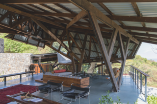 A complex, angled structure shades and protects the main outdoor living space.