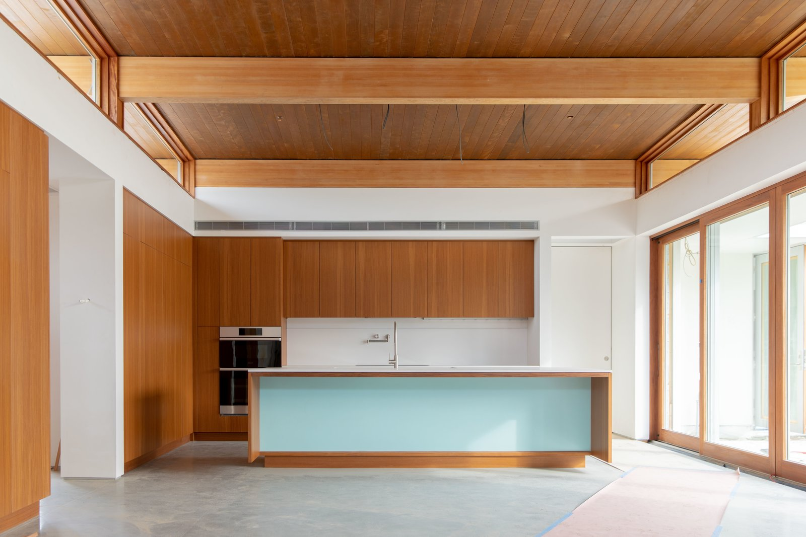 """Kitchen and Wood Cabinet For over a decade, Joel and Meelena Turkel of Turkel Design have been """"continually evolving the notion of what a home should be—maximizing flexibility and energy efficiency using engineered materials in thoughtfully designed, sustainably conceived living environments."""" Here is a look inside their latest project, the Axiom Desert House, which will soon be their own family abode.  Photos from A Palm Springs Net-Zero Prefab Flaunts an Elegant, Airy Kitchen"""
