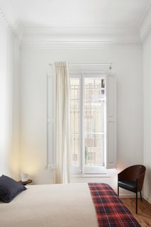 A bedroom holds a Costes chair by Philippe Starck.
