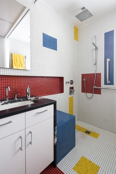 A small bathroom project inspired by artist Piet Mondrian. Floor-to-ceiling glass tiles re-interpret Mondrian's compositions.