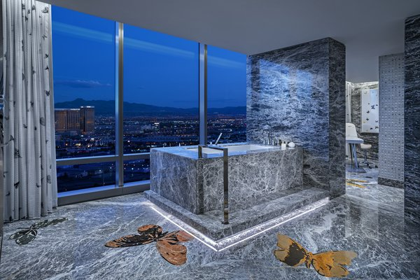 Inlaid butterflies add visual interest to the vast slabs of gray marble. An adjoining massage room makes for the ultimate spa-like bathroom.