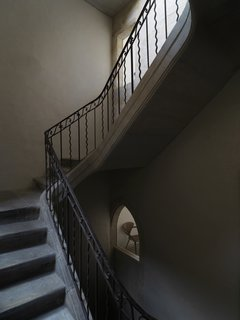The couple called in specialists TKTK to remove the steel girders that had been added to the original stone staircase sometime in the last hundred years. A small window frames a glimpse of a Cherner armchair.