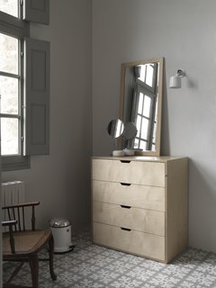 A chest of drawers by Isokon Plus, as well as a Vipp pedal bin and sconce,