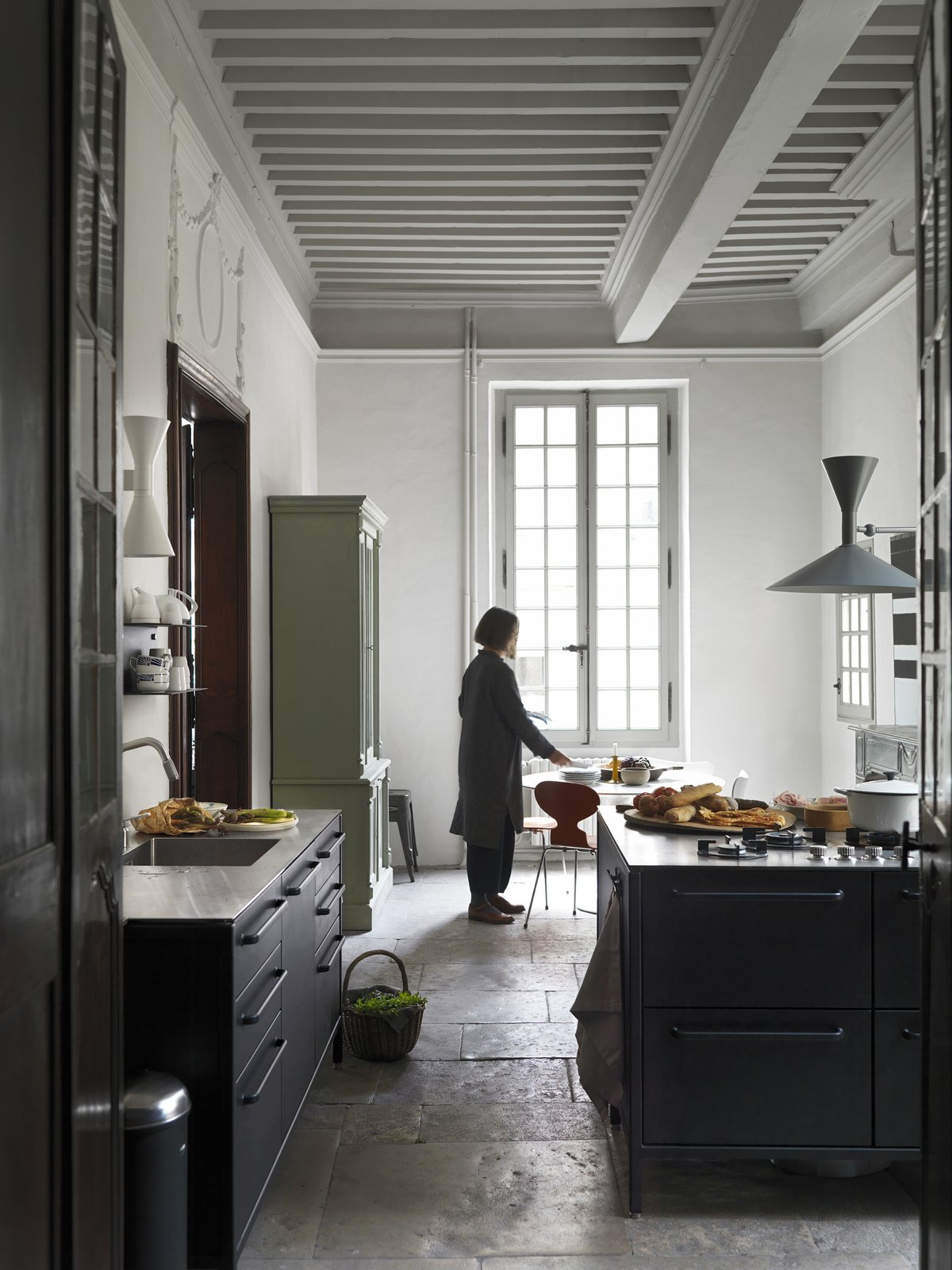 Kitchen, Metal, Metal, Wall, Drop In, Slate, and Range Lone sets the table, which is flanked by a TK. For storage, there is an antique French cabinet and shelving by Vipp.  Best Kitchen Photos from See What Happens When Two Hardcore Modernists Are Let Loose in a Medieval Townhouse in France