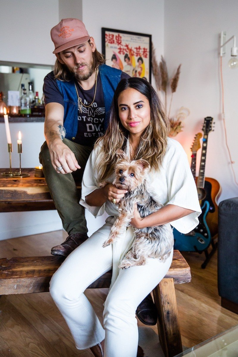 """Cyndi with her husband and their pup in their one-bedroom apartment in the West Village. Infused with some of the same chic, calming vibes she's incorporated at Chillhouse, Cyndi has also designed the space with her husband's style in mind. """"I am more eclectic with my tastes,"""" she explains, """"so it's been a fun process trying to merge our styles into one.""""  Photo 4 of 8 in Chillhouse Founder Cyndi Ramirez Reveals How to Create Cool, Collected Bathroom Vibes"""