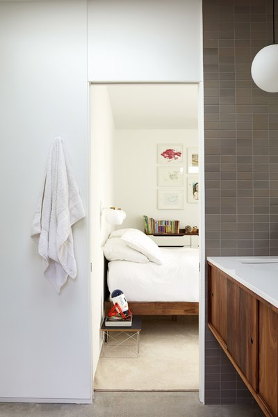 Among Jessy's favorite original details are the door headers, which are the same width as the doors themselves. A fresh coat of white paint from Sherwin-Williams gives the house a clean look. The bathroom tile is by Heath in French Gray Manganese.