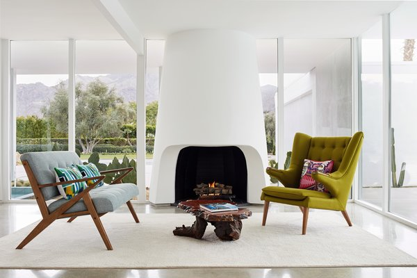 Flanked by triangular windows, the organic-shaped fireplace bears a striking resemblance to another hearth in a confirmed Cody home from the period. The couple replaced the aged floor-to-ceiling windows with more energy-efficient glazing by Monumental, while replicating the original wood stocks. The driftwood coffee table is vintage. A Berber carpet warms the concrete flooring.