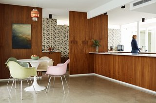 The original walnut plywood siding in the dining area and kitchen was replaced with a fresh veneer of the same wood. Recessed baseboards give the kitchen island, topped with Tk, the appearance it is floating. Various colors of Eames Molded Plastic armchairs surround a tk dining table. The pendant light is tk.