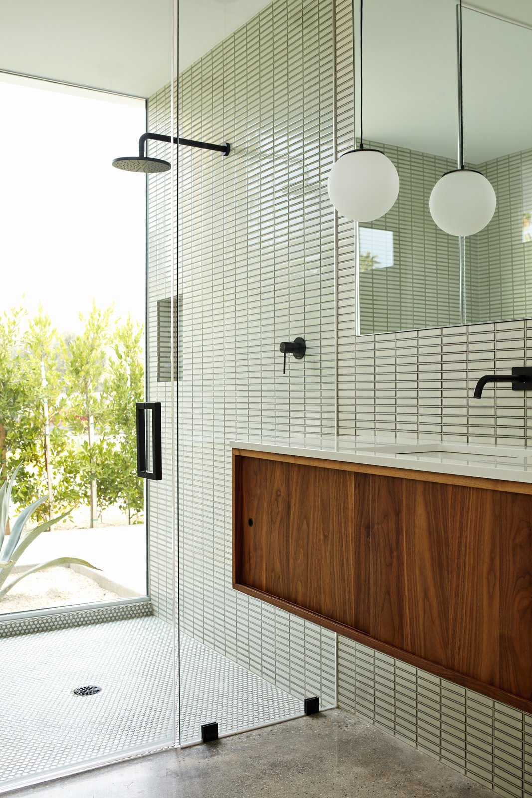 Bath, Concrete, Drop In, Enclosed, Pendant, Accent, Glass Tile, and Full New plantings provide privacy for the glass-walled shower in the master bathroom. The matte black fixtures are by Phoenix.   Bath Pendant Accent Photos from Ex Alt-Rockers Revive a Midcentury Gem Near Palm Springs—and Find it May Be a Lost Masterpiece