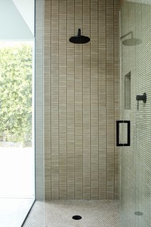 The shower is covered in Cottonwood mosaic and penny tiles by Ann Sacks.