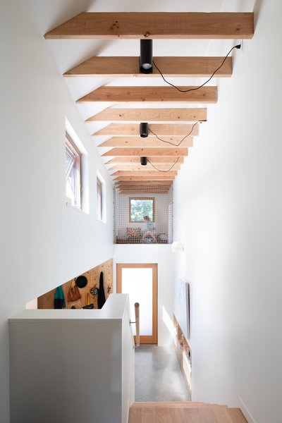 "Above the front entrance, the architects inserted a netted play area in a spot that, according to Karen, would have otherwise been a ""dust collector."" On the top level, the flooring switches from concrete to maple."