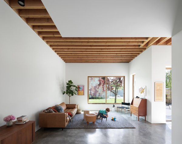 Douglas fir beams, some of which were salvaged from the original home that sat on the property, run in perpendicular lines overhead. Certain sections of the ceiling are exposed, while others are covered in drywall. For flooring, the residents, who have two young children, selected durable polished concrete. The Sven Charme sofa is by Article and the teak bureau is vintage.