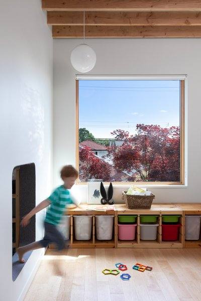 The two kids' rooms are connected by a child-sized hole in the wall. Cuddington notes that, when they get older, they will have the option to cover the opening with drywall if they like. A triple-glazed Loewen window looks out at a fiery red maple. The globe lamp is by Seagull Lighting.