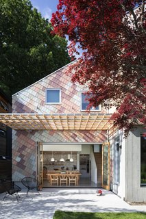Karen James and Daniel Freeman's home is a vibrant new addition to a block of midcentury bungalows in Vancouver, British Columbia. One of the volumes is clad in untreated tongue-and-groove Western red cedar. The other is covered in multicolored cedar shakes, which are skewed at an angle that aligns with the slope of the roof. Architect Clinton Cuddington of Measured Architecture worked with the owners to fine-tune the unconventional pattern and color palette.