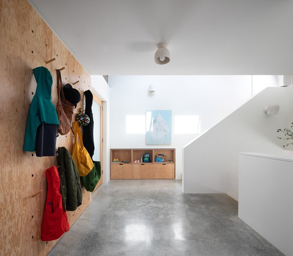 """Due to the grade of the site, the front door opens onto a landing between staircases. A wall-sized pegboard made of Douglas fir plywood is used for hanging coats, bags, and other necessities. """"The house is like a well-tailored suit that addresses a range of daily routines,"""" Cuddington observes."""