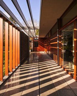 Together, the louvered sections of fence and the trellised roof overhangs paint the breezeway with shadows.