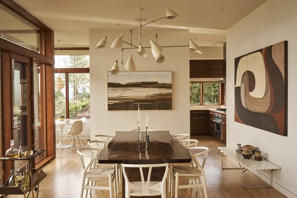 Removing a wall between the living and dining areas greatly improved the flow of the main level. The live-edge walnut dining table was made by Goby Walnut and the Wishbone chairs are by Hans Wegner.