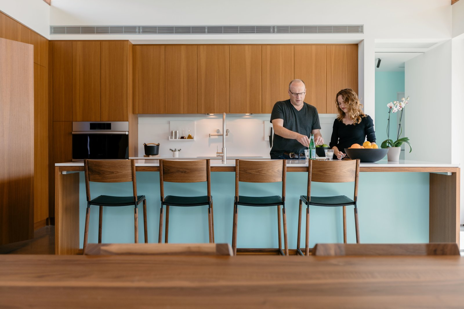 "Kitchen, Accent Lighting, Wood Cabinet, Drop In Sink, Wall Oven, Refrigerator, and Concrete Floor When it came time to select appliances that would seamlessly blend into their kitchen, Joel and Meelena relied heavily on Dacor for their elegant, high-tech product line. ""What I love about the camera in the fridge is that it's highly functional and not just a gimmick,"" notes Joel. ""How many times have you gone to the store and purchased things because you forgot you had it? In my mind, this is a beautiful, simple feature that allows you to use less and waste less—while also wasting less time.""  Photos from Step Inside Palm Springs' Latest Indoor/Outdoor Prefab Home"