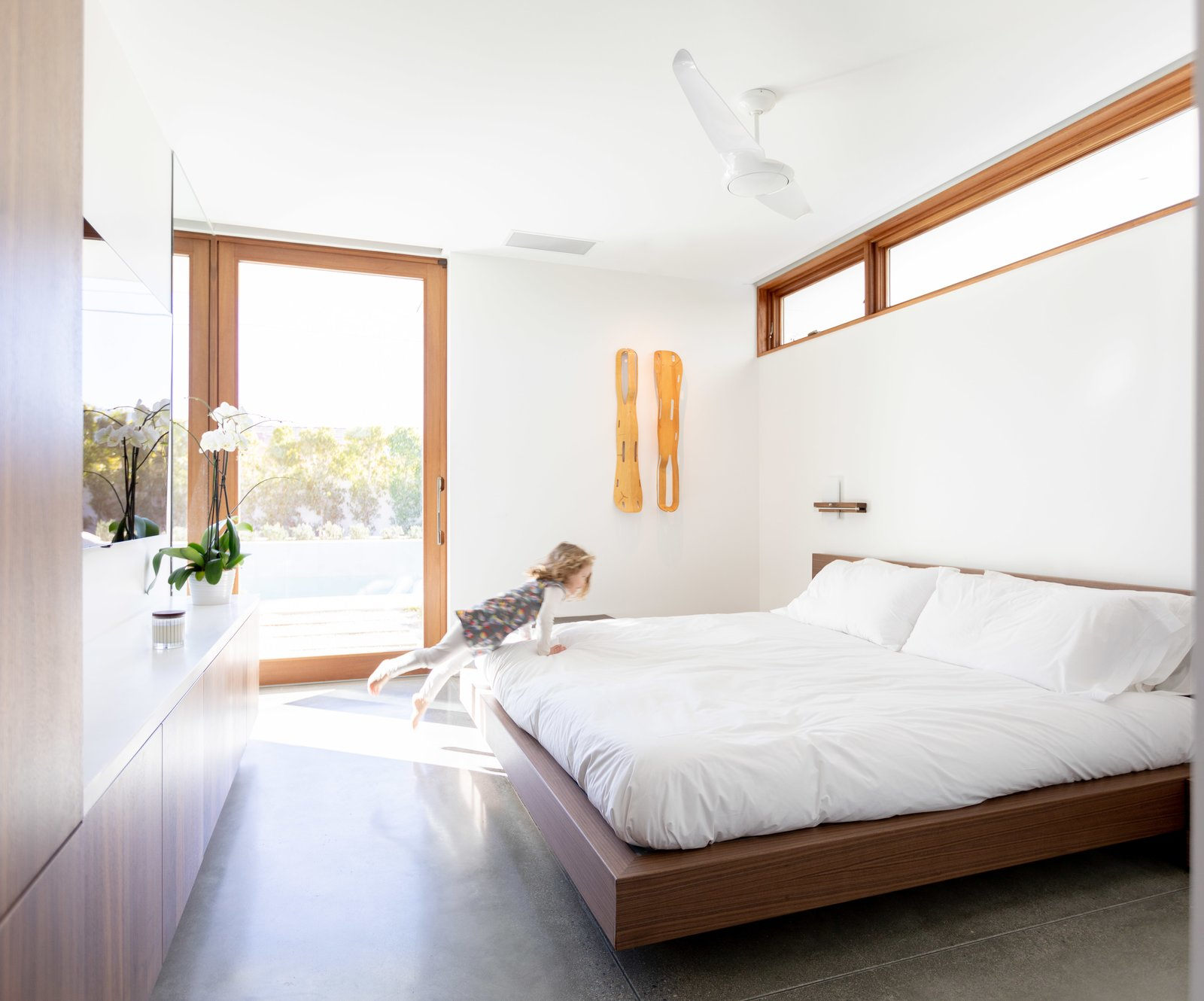 """Bedroom, Bed, Accent Lighting, Wardrobe, and Ceiling Lighting Thanks to the efficiency of the bedroom fans by The Modern Fan Co., the Turkels can keep the Marvin lift-and-slide doors open throughout much of the year without having to rely on air conditioning. """"We want to be able to keep the doors open as much as possible, yet sometimes the air movement in the desert isn't sufficient to counteract the heat, so the fans are really a must,"""" adds Meelena.  Photo 7 of 8 in Step Inside Palm Springs' Latest Indoor/Outdoor Prefab Home"""