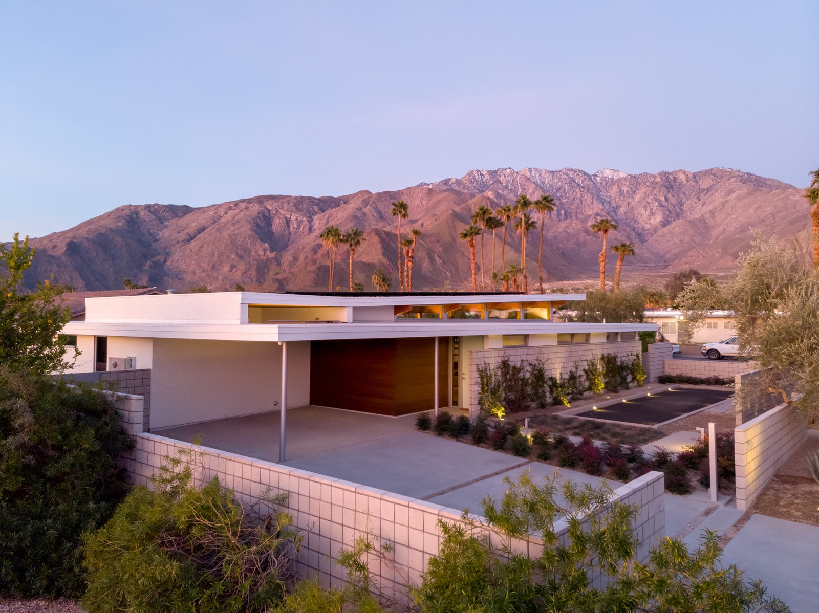 Exterior, Prefab, House, Concrete, Flat, Stone, Stucco, and Metal A peek of the Axiom Desert House from the exterior, with the beautiful San Jacinto mountain range in the distance.  Exterior Stucco Concrete Stone Photos from Step Inside Palm Springs' Latest Indoor/Outdoor Prefab Home