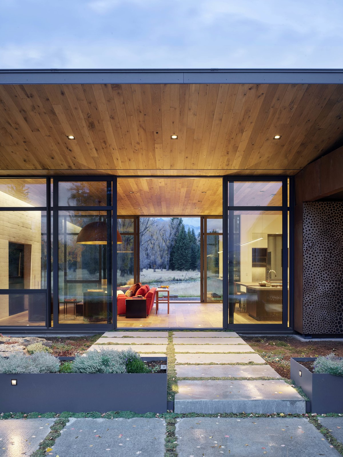 Outdoor, Hardscapes, and Raised Planters Window walls grace the north and south sides of the building, illuminating the open-plan living and dining area. A fireplace caps off one end of the long room.  Photo 5 of 11 in A Museum-Like Glass Pavilion Brightens a Sprawling Jackson Hole Estate
