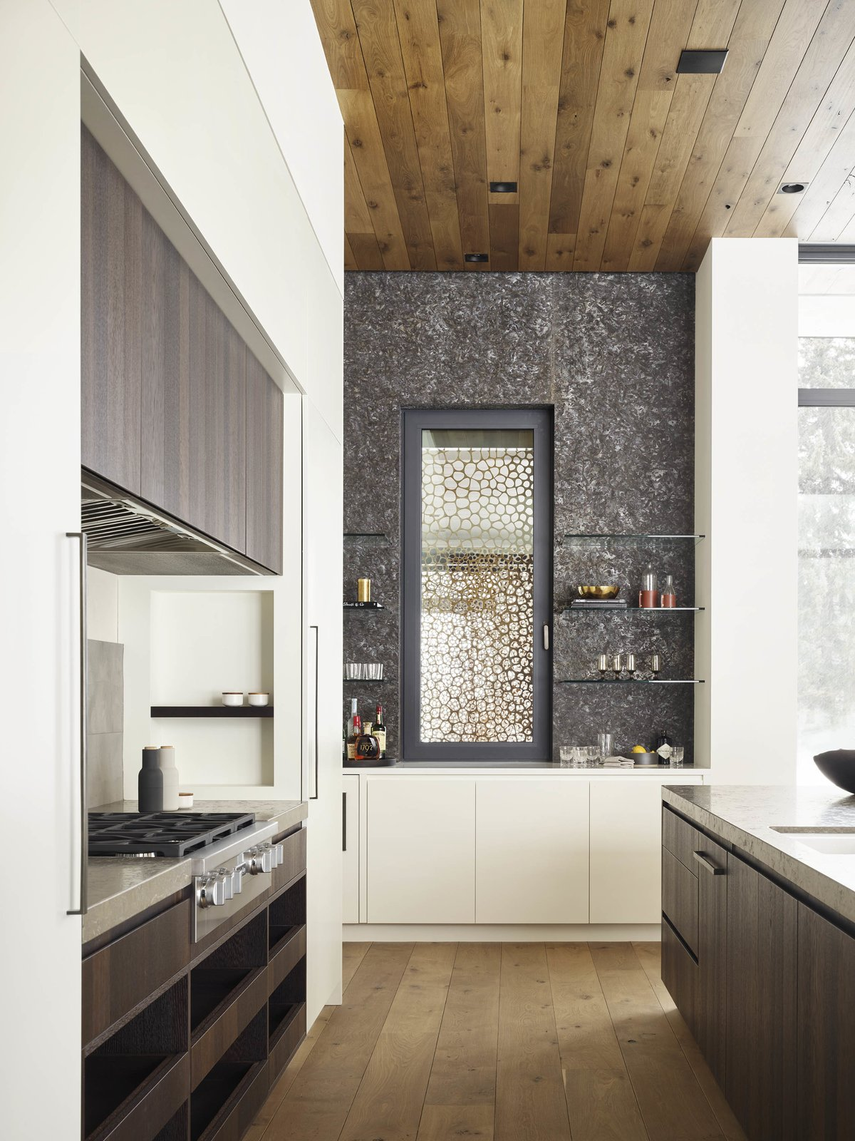 Kitchen, Medium Hardwood Floor, Marble Counter, and Wood Cabinet White oak, dressing the ceilings and floors, unifies the different spaces.  Photo 7 of 11 in A Museum-Like Glass Pavilion Brightens a Sprawling Jackson Hole Estate