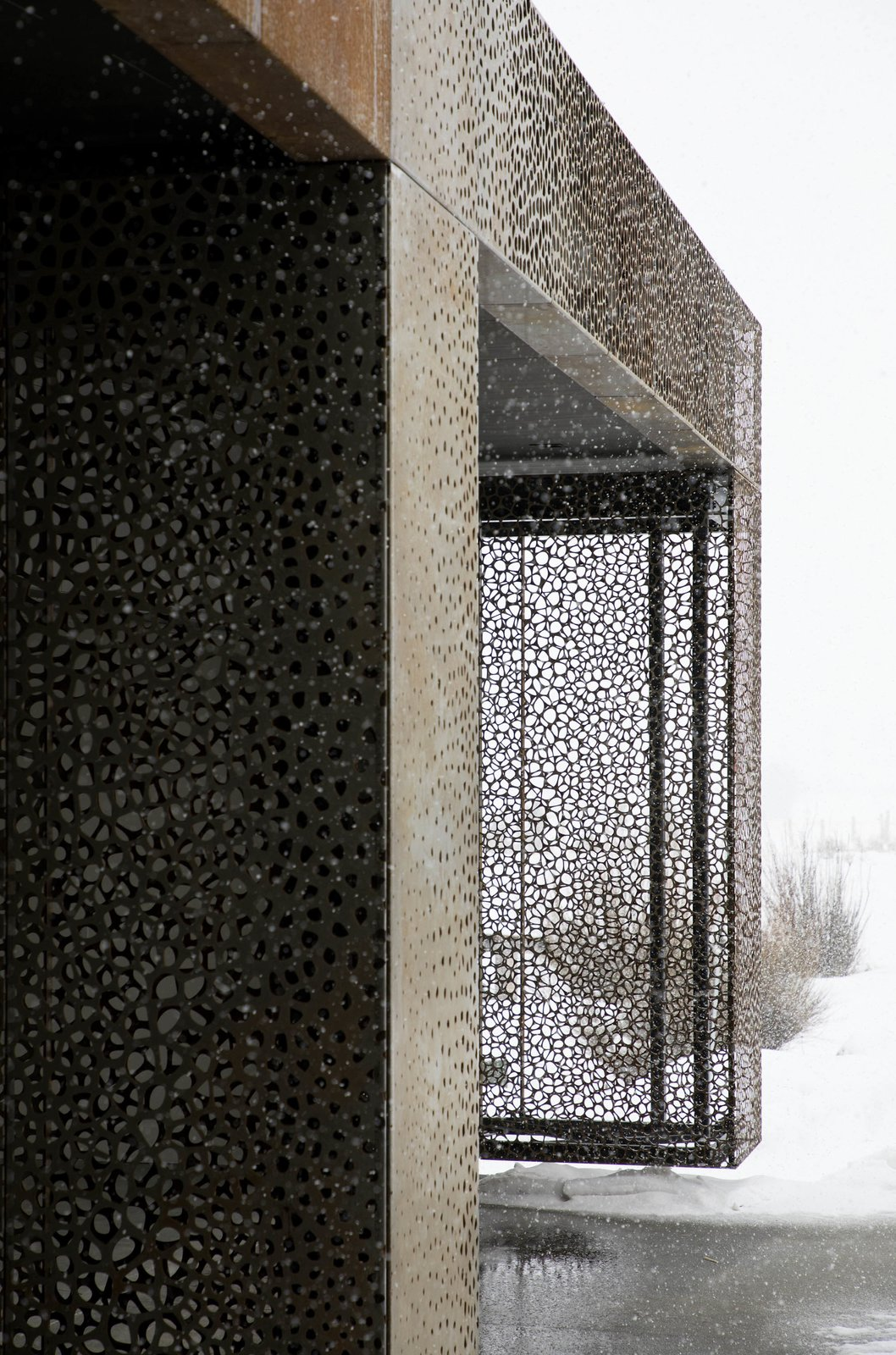 Exterior, Metal Siding Material, Flat RoofLine, and House Building Type The intricate metal curtain doubles as a work of art.  Photo 9 of 11 in A Museum-Like Glass Pavilion Brightens a Sprawling Jackson Hole Estate