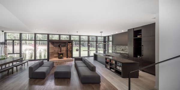 The abundance of natural light drifting in from above is enhanced in the first-floor communal areas, where the architects integrated an 11-foot-long, floor-to-ceiling window wall along the full length of the house.