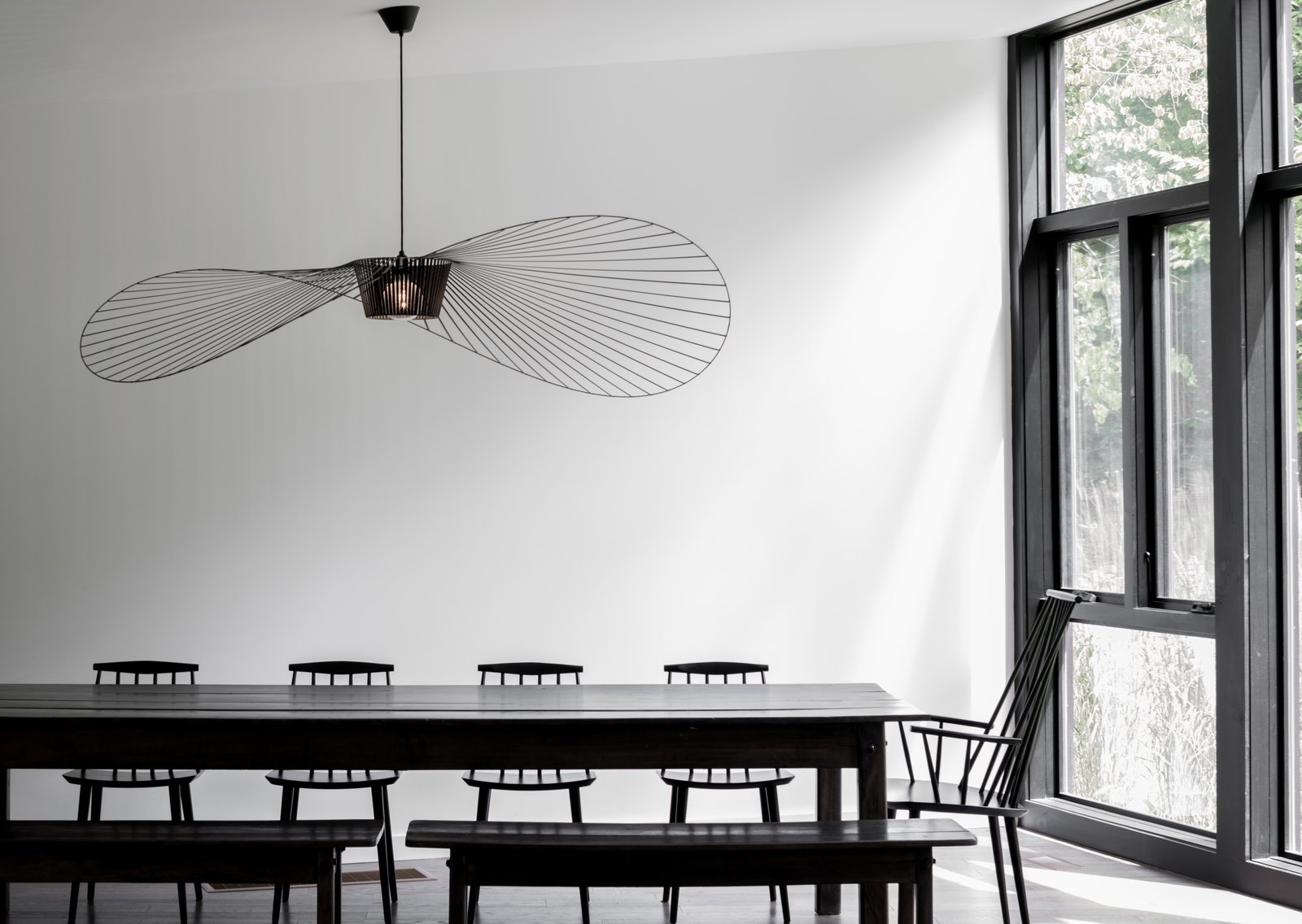 Dining Room, Table, Pendant Lighting, Chair, and Bench With Marvin floor-to-ceiling windows incorporated throughout, the home not only blurs the barriers between inside and out, it also fosters a deeper connection to nature.