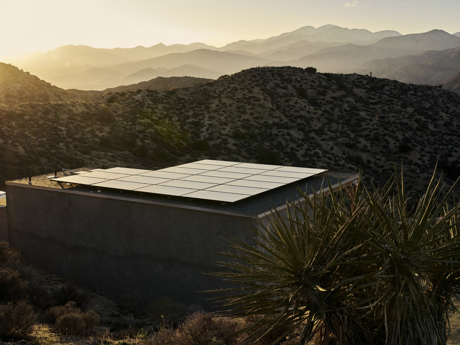 """Outdoor, Desert, and Shrubs A new structure near the dome holds an array of solar panels and three lithium-ion batteries. """"The power is completely sustainable,"""" says Sam. """"I can even run the air-conditioning on it.""""  Best Outdoor Desert Shrubs Photos from A Tech Entrepreneur Rehabs an Off-Grid Dome Home in Joshua Tree"""