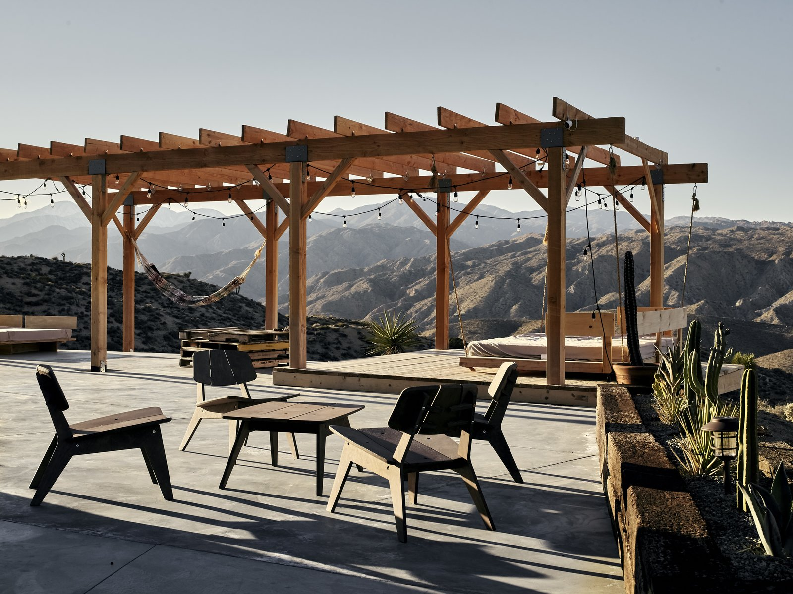 Outdoor, Large Patio, Porch, Deck, Back Yard, Shrubs, Hanging Lighting, Wood Patio, Porch, Deck, and Concrete Patio, Porch, Deck A cement slab and wood deck offer space for meals and stargazing. Sam built the furniture himself.  Photos from A Tech Entrepreneur Rehabs an Off-Grid Dome Home in Joshua Tree