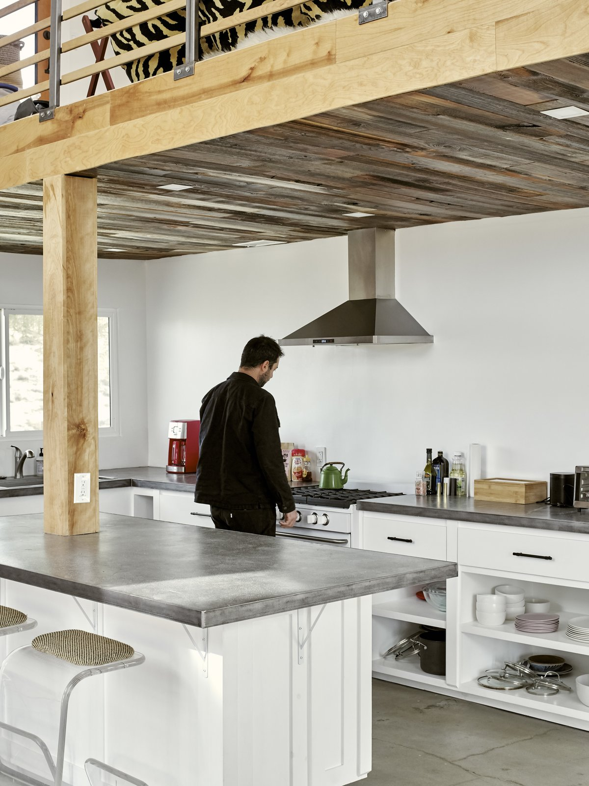 Kitchen, Concrete, Range Hood, Range, Concrete, and White The kitchen is outfitted with concrete counters and floors and off-grid-friendly appliances that use less energy. The ceiling is paneled in reclaimed barn wood.  Best Kitchen Concrete Concrete Photos from A Tech Entrepreneur Rehabs an Off-Grid Dome Home in Joshua Tree