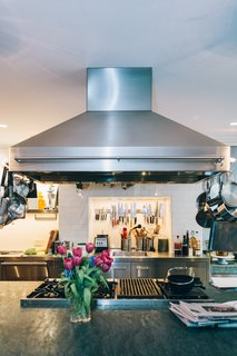 """""""Along one wall of our rectangular kitchen, we have stainless-steel counters with a small prep sink, a large, deep sink for washing, and two dishwashers. On the other side, we have a small bar sink with a coffee maker and banquette,"""" Ted explains. """"Our double-oven is in the center under the vent hood. Over the years, I've learned ventilation is key in the kitchen. There's so much you can't do if you don't have proper ventilation—like pan-fry a steak."""""""