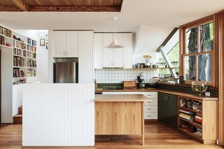 In the kitchen, Barker offset painted and natural plantation wood with green Inax Biyusai and white Waringa tiles. The pendant is by Gubi.