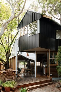 Working around mature eucalyptus and elm trees, architect Murray Barker sited a new home for Fleur Glenn on her property in Clifton Hill, Australia. The trees also drove the home's shape, with angles meeting the gabled roof in unexpected ways. The south elevation mixes black-stained timber and cement board with board-and-batten siding.