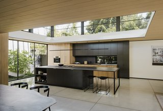 Walnut and Formica cabinetry, Neolith basalt counters, and concrete floors make up the kitchen's minimal palette; a large clerestory ushers in natural light.