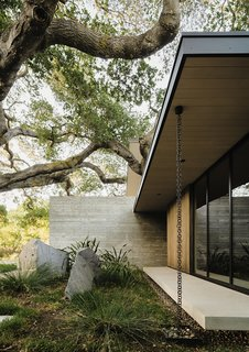 A 100-year-old oak shades the front of the house, which is clad in weathering yellow cedar.