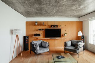 Floor lamps by Habitat and Muuto light up the living room; the gray Can armchairs are by Hay. Here and in the kitchen, the ceiling's plaster coat was removed to reveal the concrete underneath.
