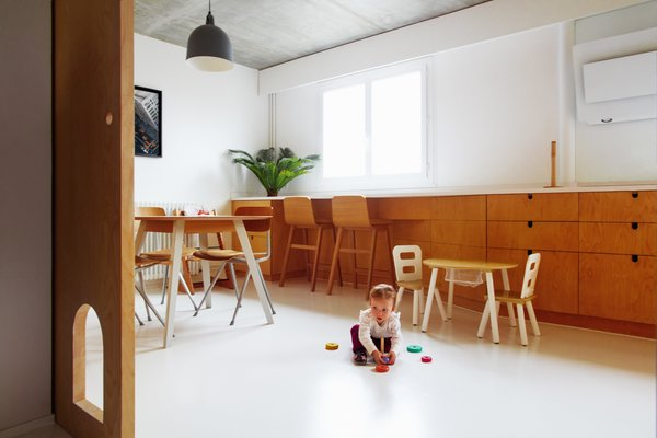 "Laura, 21 months, enjoys playing on the eat-in kitchen's white resin floor. ""We spend a lot of time in the kitchen,"" says Aurélie. ""It's the hub of our home."" The dining table is by Treku and the chairs are by Hay. Stools by Alki face windows with sweeping views of Paris. Abundant light was a priority for the couple, and the sun that comes in through windows at one end of the upper floor can reach the other end."