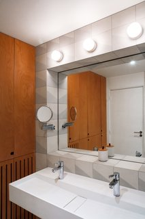 The bathroom's cement tiles, designed by Delaunay to evoke waves and made by The Mosaic Factory, frame an inset mirror.