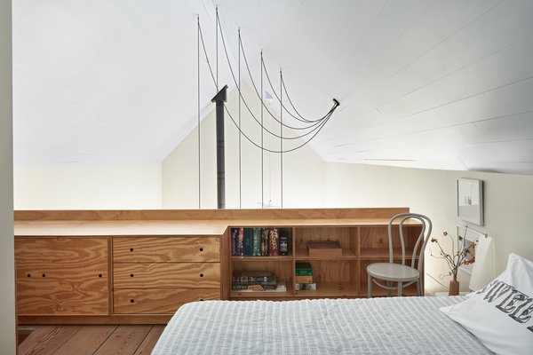 The guest loft features a bed from West Elm and custom plywood casework  by Kansas City artisan Haynes Nichols.