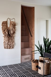 Nichols also made the steep stairwell leading up from the entryway. The straw garment on the wall is a <i>mino</i>, a traditional Japanese raincoat.