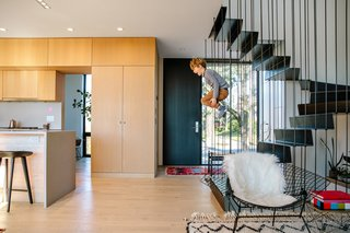 "A fuzzy white throw is draped over a Diamond chair by Harry Bertoia in the living room; the Tractor stool at the counter is by Craig Bassam. Leckie, who teamed up with Modern Organic Construction and Munzing Structural to execute the design, mostly stuck to three finishes for the two main floors: white oak, drywall, and blackened steel. Cara describes the home's design as ""quite simple—a modern Scandinavian look."""