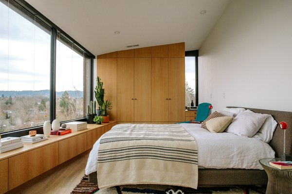 Focusing primarily on the view, the residents decorated the master bedroom with succulents, books, ceramics, and little else. A blanket from The Citizenry lies across an  Onto bed by Bensen.