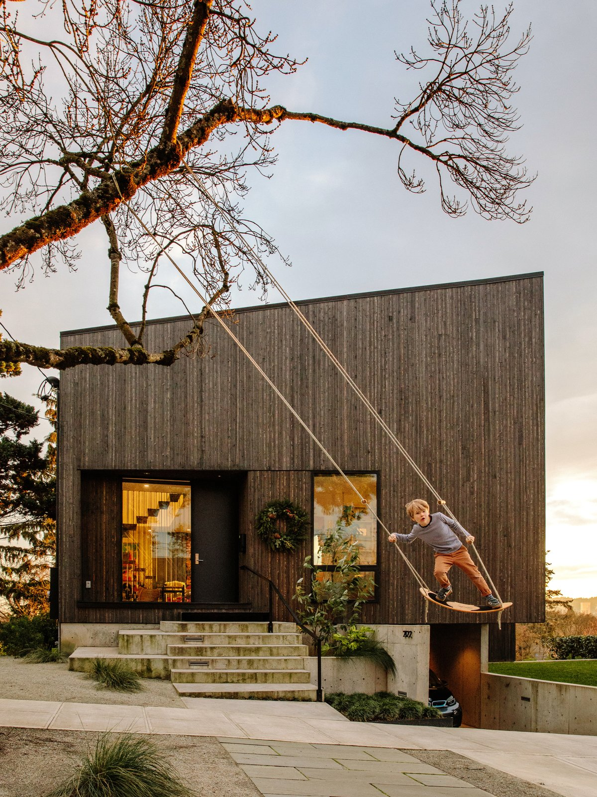 """Exterior, Shed RoofLine, House Building Type, and Wood Siding Material In 2013, Jennifer Warner and Cara Frey fell in love with a modest but charming 1920s house within walking distance of their bungalow. The dwelling was dramatically sited, with great views of Portland's southwest hills and downtown. But according to Michael Leckie, the Vancouver–based architect they eventually hired, """"It was the dumpiest house on the block."""" Leckie replaced the house with a simple, modern design, using a basic square wood box that skews into a rhombus form, which he topped with a sloping roof. Their son, William, 6, swings in front of the cedar-clad house.  Best Photos from A Darkened Cedar Dwelling in Portland Embodies """"Less But Better"""" Design"""