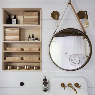 """Bamboo bathroom caddies from Muji complement a leather-bound mirror by Jacques Adnet for Gubi. In keeping with the home's old-new dynamic, a 1920s vintage Kohler sink is furnished with a brushed gold faucet from Kohler's Purist Collection. """"The process of remodeling reflected a discovery, a real blending,"""" says Jennifer."""