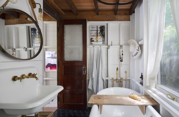 A cast-iron tub from Signature Hardware sits beneath a large window; the unlacquered brass faucet is from Waterworks.