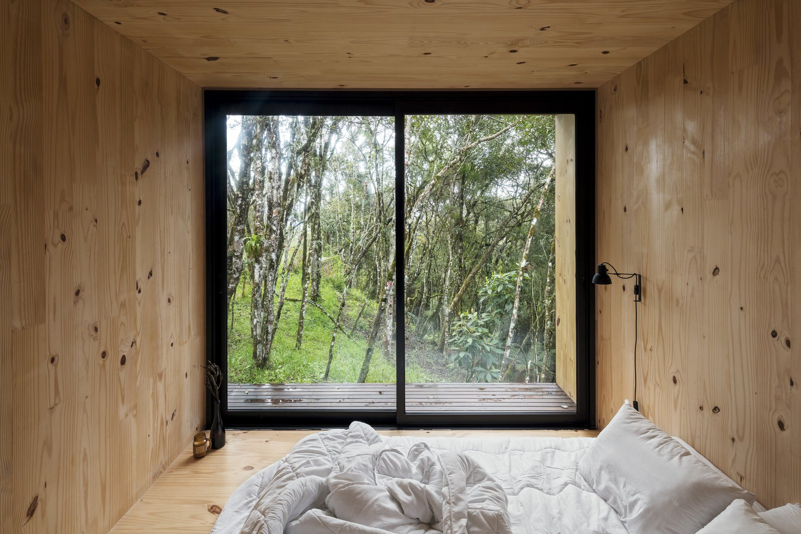 """Bedroom, Wall Lighting, Light Hardwood Floor, and Bed Sliding glass doors in the bedroom make the most of the cabin's location. """"The weather is incredible,"""" notes Ralph. """"Summers are not very warm, and it's rarely cold in winter.""""  Photo 5 of 9 in A Brazilian Couple's Prefab Cabin Is the Perfect Outpost for Forest Bathing"""