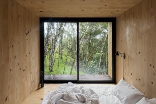 "Sliding glass doors in the bedroom make the most of the cabin's location. ""The weather is incredible,"" notes Ralph. ""Summers are not very warm, and it's rarely cold in winter."""
