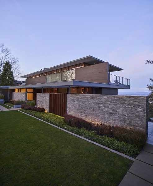 "From the front, Greg Hoffman and Kirsten Brady's home in Portland, Oregon, bears little resemblance to the daylight ranch house that once stood in its place. Yet upon closer inspection, it is clear that the enlarged structure is actually an updated version of the same dwelling that has occupied the site since the early 1950s. More windows, a trellised roofline, a basalt privacy wall, and a flat-roofed, top-floor addition are among the most striking changes. Plantings were also added to enhance the yard. ""There was zero landscaping,"" says Greg, ""If you look at the original photos, the house was just sitting on the ground."" All of the new features are carefully oriented so that the sightline from the street through the house to the vista beyond remains open. ""The original house had a gap in the hedge so people could see the view,"" Greg recalls. ""We said, 'Let's keep that.'"""